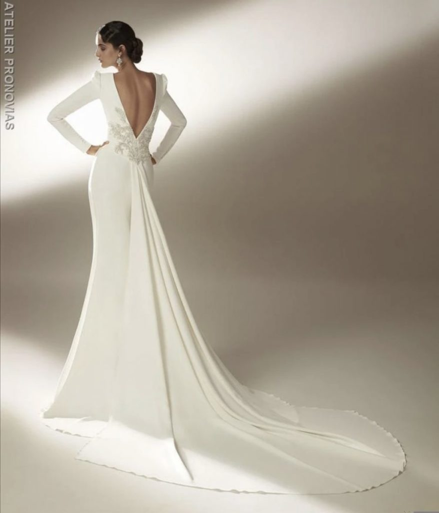 Back view of woman wearing a modern and simple crepe wedding dress with low back