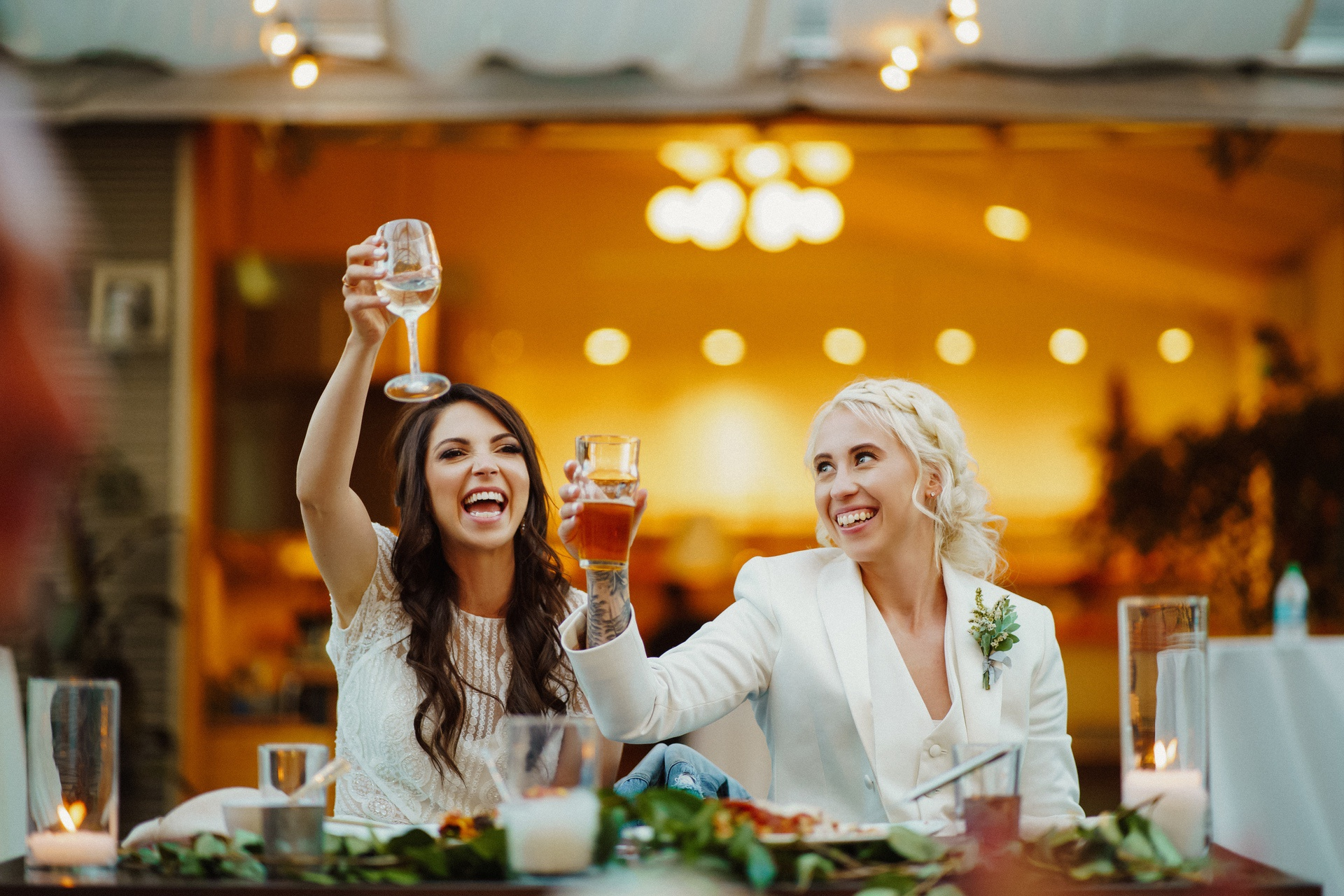 Smiling wedding guests lifting glasses during toast